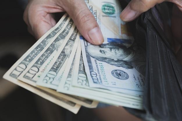 Main tenant un billet de banque dans le portefeuille pour le concept financier, comptable et épargne.