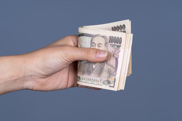 Main tenant un billet de banque japonais