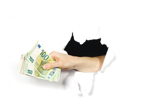 Main tenant des billets en euros à travers un trou