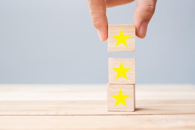 Main tenant des blocs de bois avec le symbole de l'étoile. avis des clients, commentaires, évaluation, classement et concept de service.
