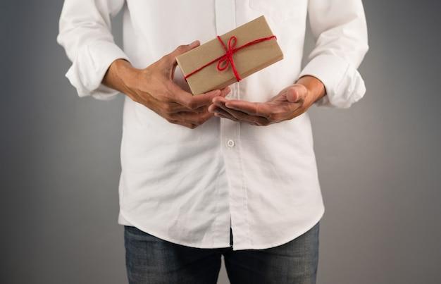 Main tenant une boîte-cadeau, une boîte-cadeau de nouvel an, une boîte-cadeau de noël, un espace de copie. noël, nouvel an, concept d'anniversaire.