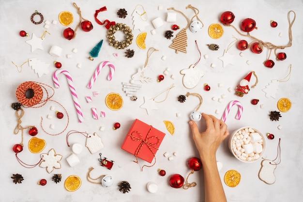 Main tenant une boîte cadeau emballée. décoration de noël avec coffrets cadeaux, corde, guimauves, biscuits au pain d'épices