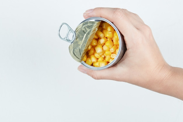 Main tenant une boîte de conserve de maïs sucré bouilli.