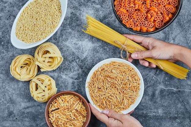 Main tenant un bol de pâtes sèches avec différents types de pâtes crues sur la table en marbre.