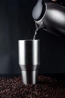 Main tenant une bouilloire électrique et versant de l'eau dans un gobelet en acier inoxydable de café noir chaud sur un tas de graines de café sur fond noir.