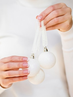 Main tenant des boules de noël blanches