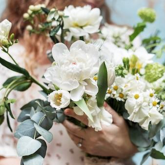 Main tenant un bouquet blanc