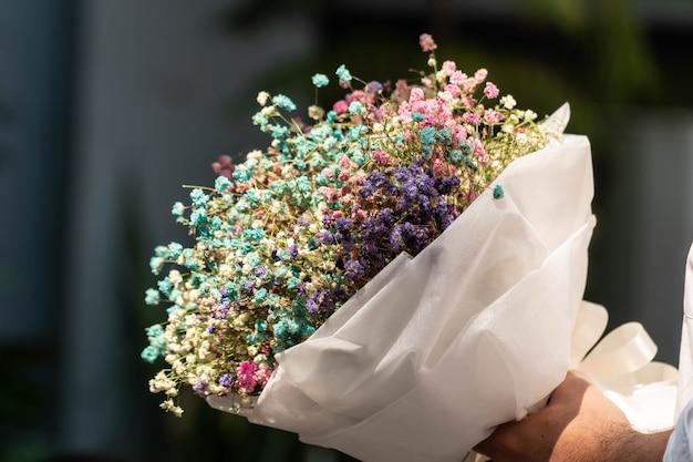 Main tenant un bouquet de fleurs de gypsophile séchées enveloppées dans du papier