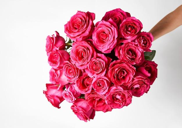Main tenant un bouquet de roses roses sur fond blanc avec espace de copie.