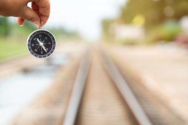 Main tenant la boussole en arrière-plan de chemin de fer
