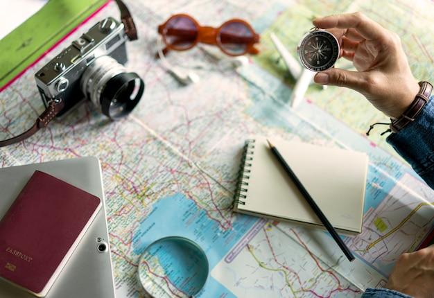 Main tenant une boussole pour planifier un voyage de vacances et des accessoires pour voyager