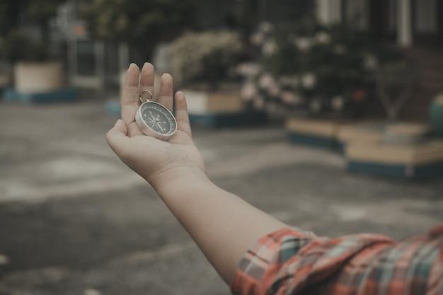 Main tenant une boussole pour trouver des destinations de voyage. style vintage.