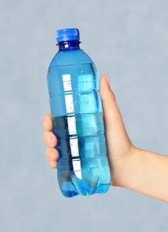 Main tenant une bouteille bleue avec de l'eau
