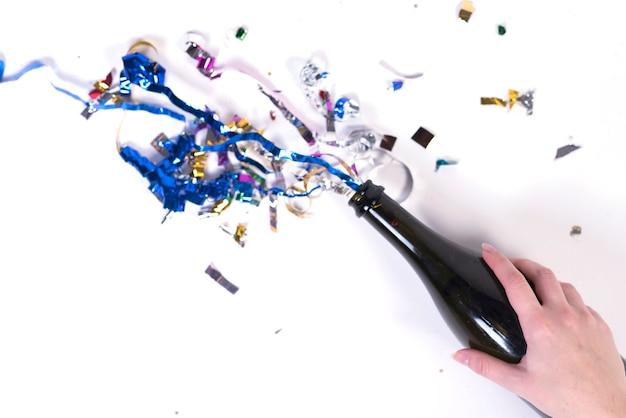 Main tenant une bouteille avec des confettis qui sortent