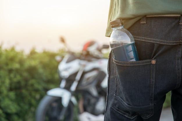 Main tenant une bouteille d'eau avec un gros vélo, vacances d'été en plein air et vue en soirée
