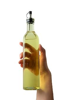 Main tenant une bouteille d'huile sur blanc. ingrédients de cuisine. huile isolée.