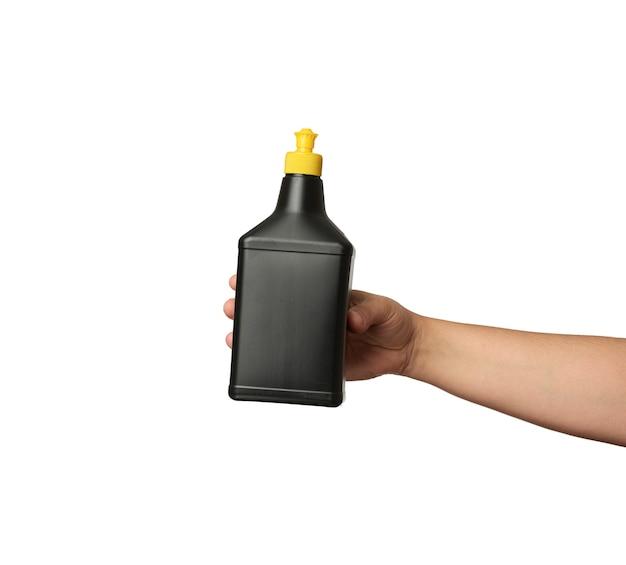 Main tenant une bouteille en plastique noir avec un détergent