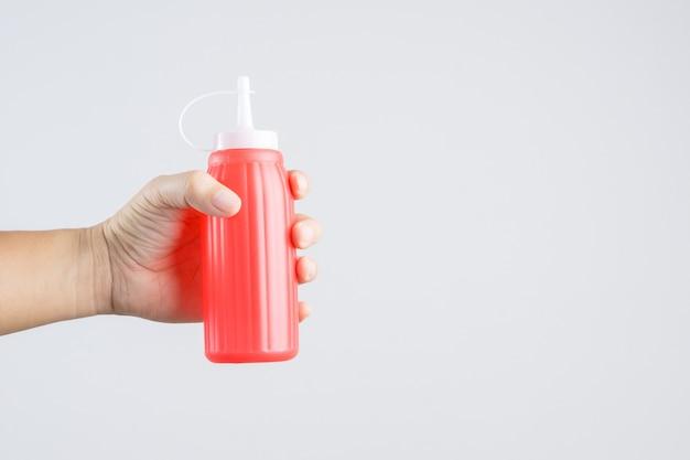 Main tenant une bouteille de sauce rouge pour le ketchup ou le piment rouge
