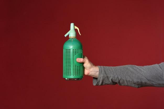 Main tenant une bouteille de siphon sur fond rouge