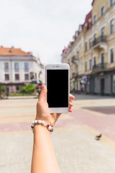 Main tenant le bracelet tenant le smartphone à la rue