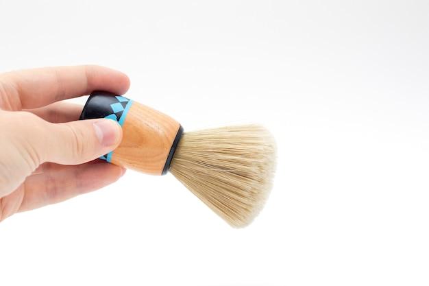 Main tenant une brosse pour se raser la barbe.