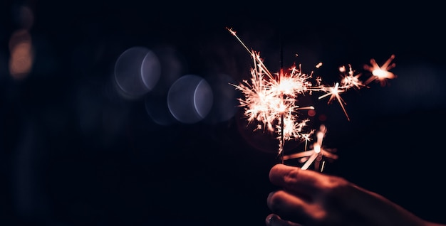 Main tenant brûlant explosion de sparkler sur un fond noir de bokeh pendant la nuit