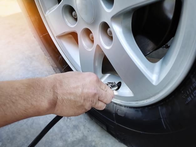 Main tenant la buse pendant le gonflage des pneus avec mise au point sélective