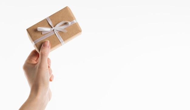 Main tenant un cadeau avec un arc et un espace de copie