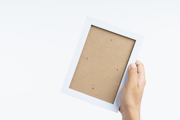Main tenant un cadre en bois blanc
