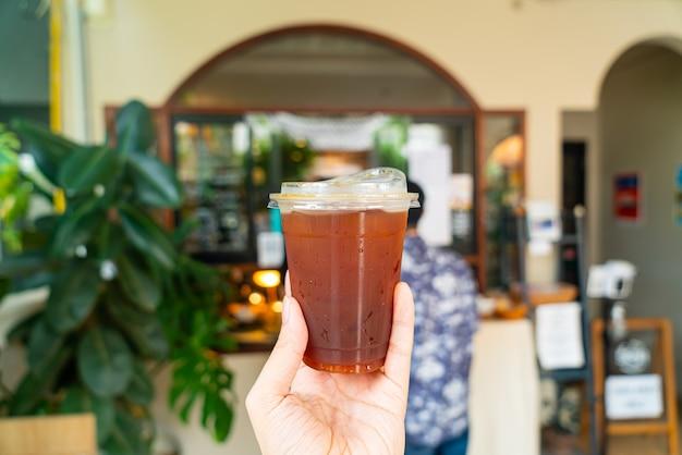 Main tenant un café americano glacé dans un verre à emporter