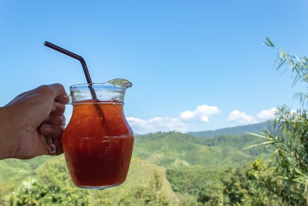 Main tenant un café noir glacé dans un bocal en verre et vue sur la montagne.