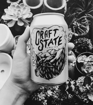 Main tenant la canette de bière de l'état de l'artisanat avec fond de plantes d'intérieur