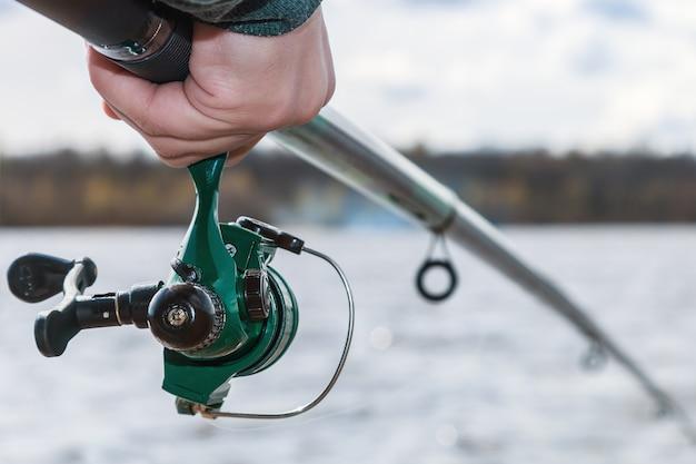 Main tenant une canne à pêche avec moulinet