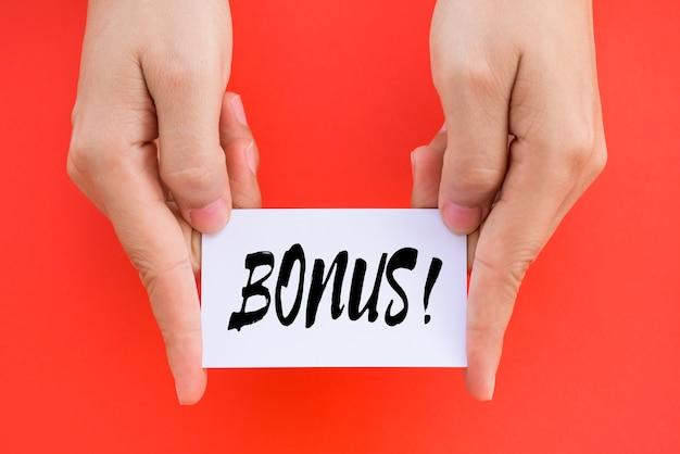 Main tenant la carte bonus avec un fond rouge.