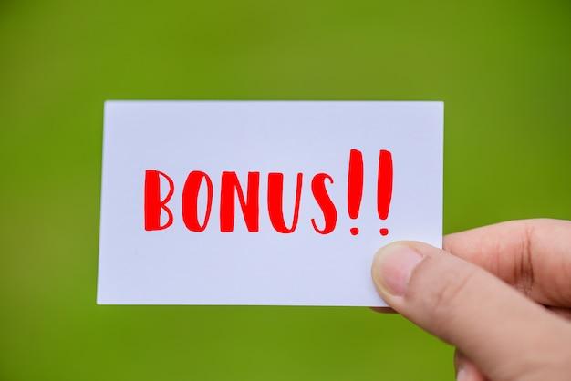 Main tenant la carte bonus avec fond vert