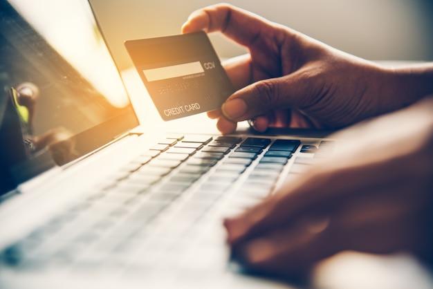 Main tenant une carte de crédit dans leurs mains et trouver des informations sur un produit à l'aide de leur appareil mobile
