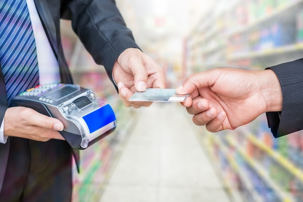 Main tenant une carte de crédit avec un homme d'affaires utilisant un terminal de paiement sur fond de magasin de supermarché