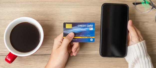 Main tenant une carte de crédit pour faire des achats en ligne sur smartphone pendant que vous buvez du café. joyeux réveillon de noël, décembre, saisonnier, vente du vendredi noir, concept de nouvel an et de vacances