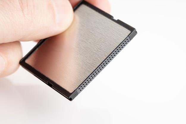Main tenant une carte mémoire compactflash sur une surface blanche. matériel photographique. copier l'espace