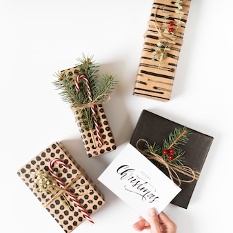 Main tenant la carte de noël au-dessus des coffrets cadeaux
