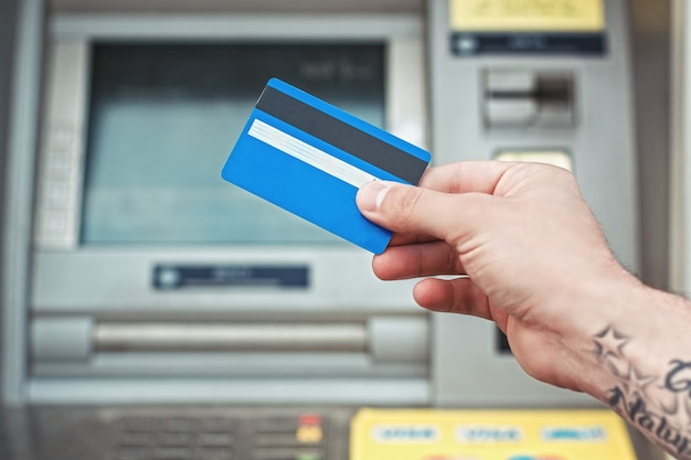 Main tenant une carte en plastique près d'un guichet automatique