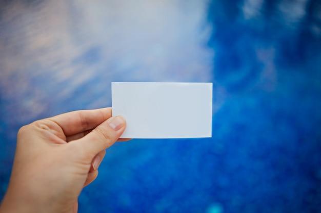 Main tenant une carte de visite sur le fond d'une jetée sur la plage