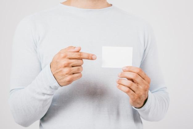 Main tenant carte de visite et pointage du doigt