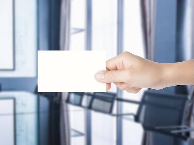 Main tenant une carte de visite vierge avec fond de bureau