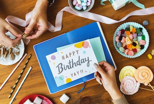 Main tenant une carte de voeux d'anniversaire sur fond de table en bois avec des collations sucrées