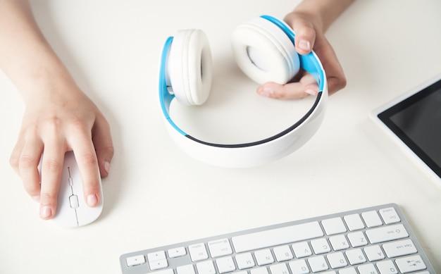 Main tenant un casque au bureau. écouter de la musique