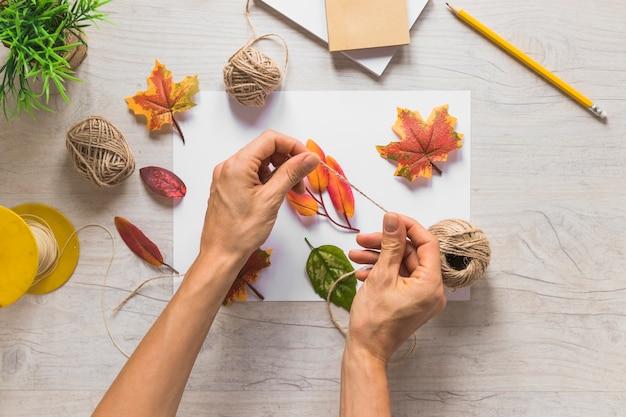 Main tenant une chaîne avec de fausses feuilles d'automne sur du papier blanc sur le fond texturé
