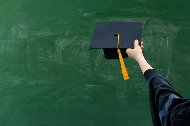 Main tenant le chapeau de graduation sur tableau vert