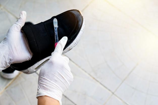 Main tenant la chaussure et nettoyage avec une brosse à dents.