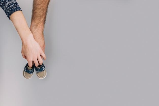 Main tenant des chaussures de bébé